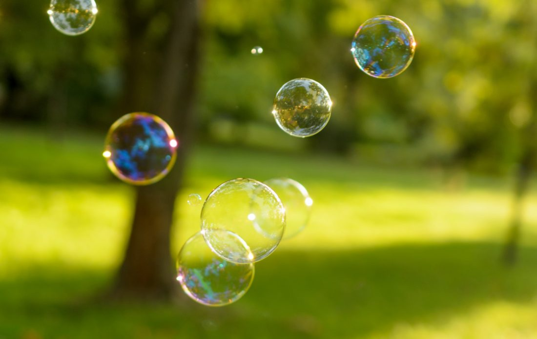 Bubbles float on a green lawn at sunset.
