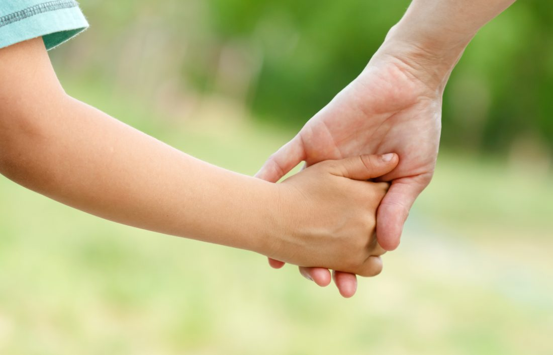 Mother holds the hand of her child